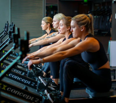 Women rowing on indoor rowing machines during one of the many available workout classes in Nashville