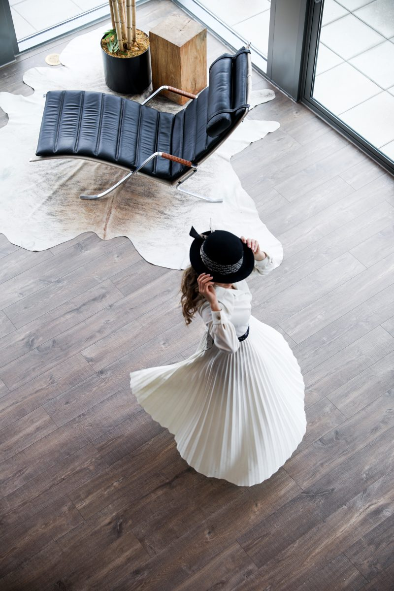 Celine in a pleated white dress with a black hat