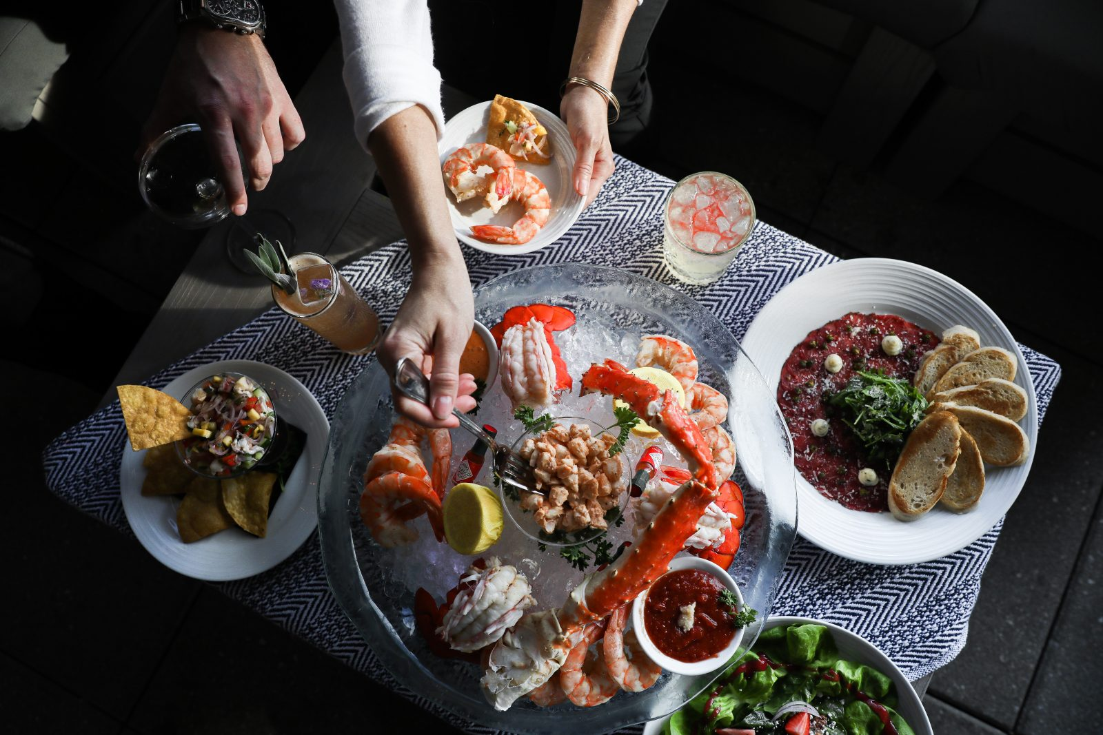 Shrimp platter, crab legs, and drinks at this patio dining location