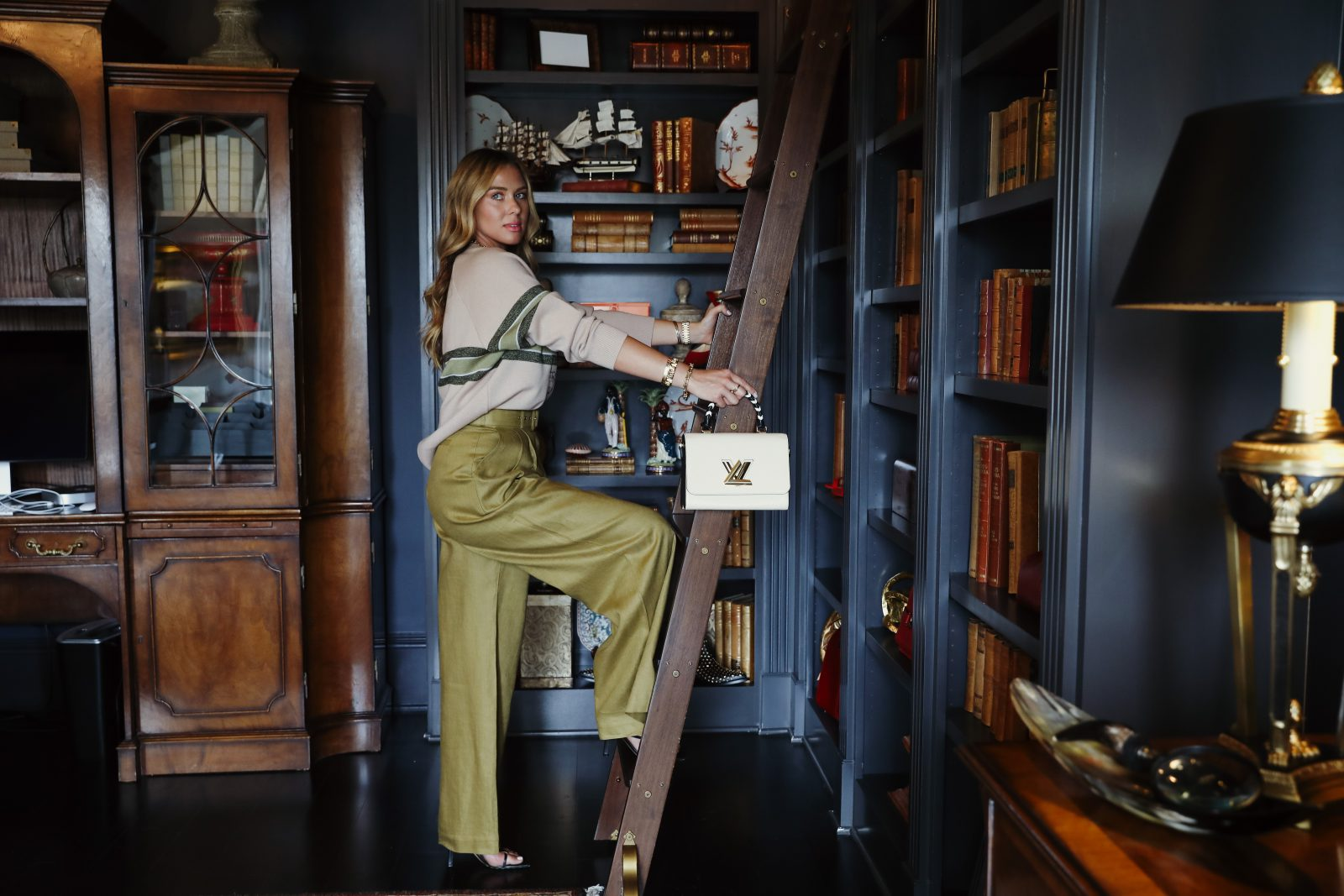 Vintage library photoshoot with Elizabeth Allen in olive dress pants