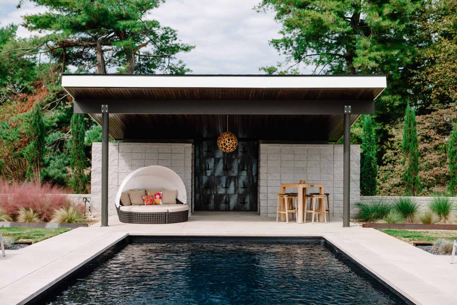 Outdoor cabana space next to a pool