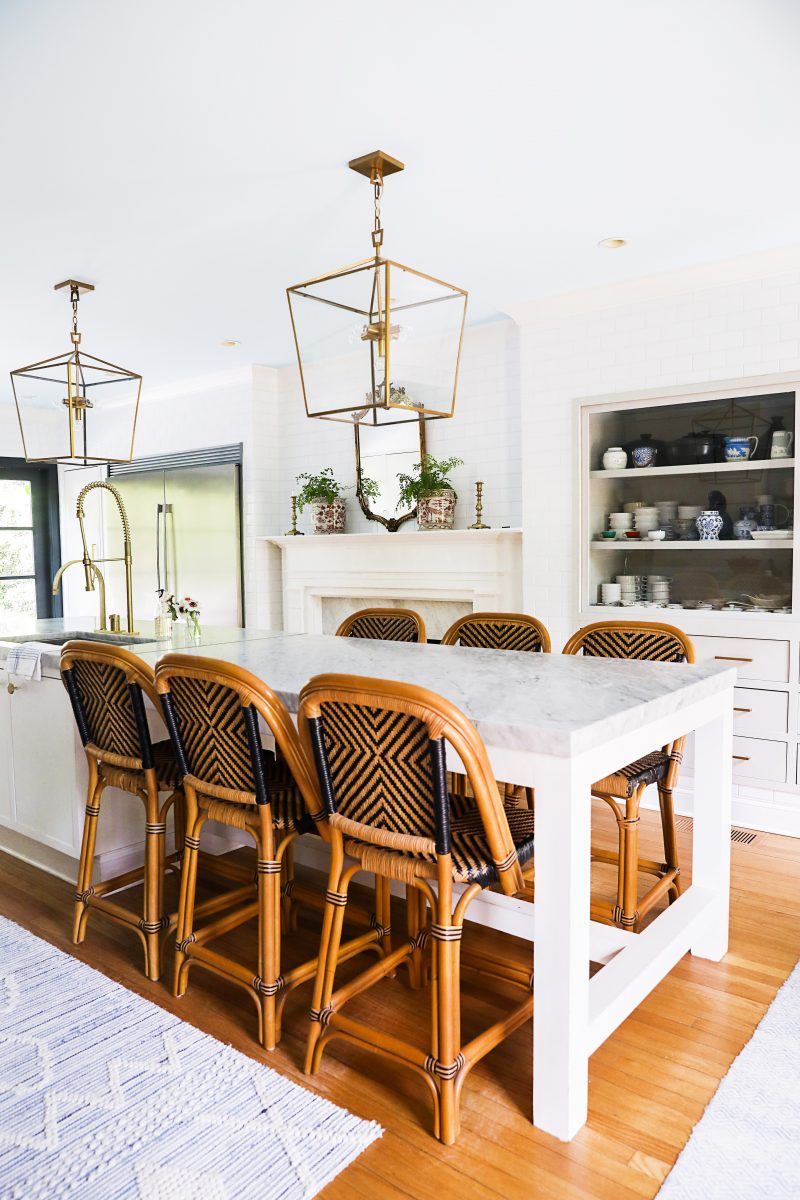 white aesthetic kitchen with gold and bronze accents and wicker chairs