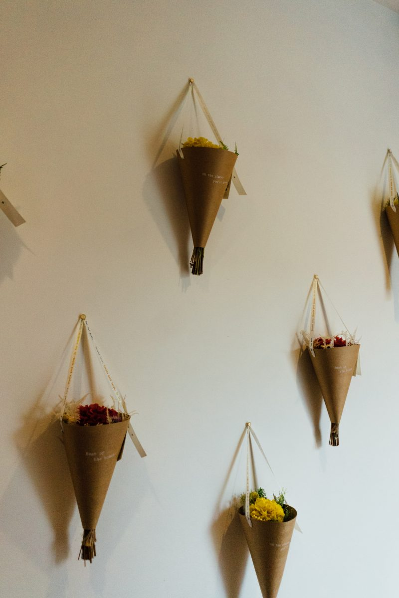 Flowers in paper cones hung on a wall
