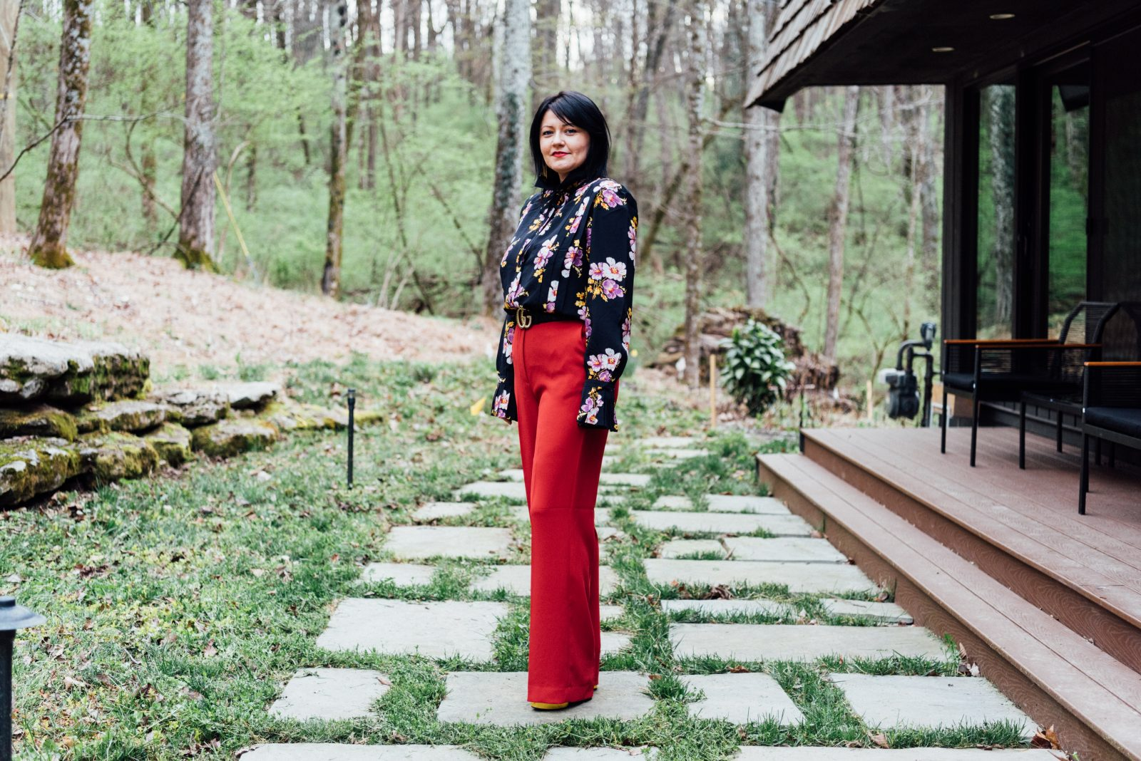 Woman with a black floral shirt and red pants