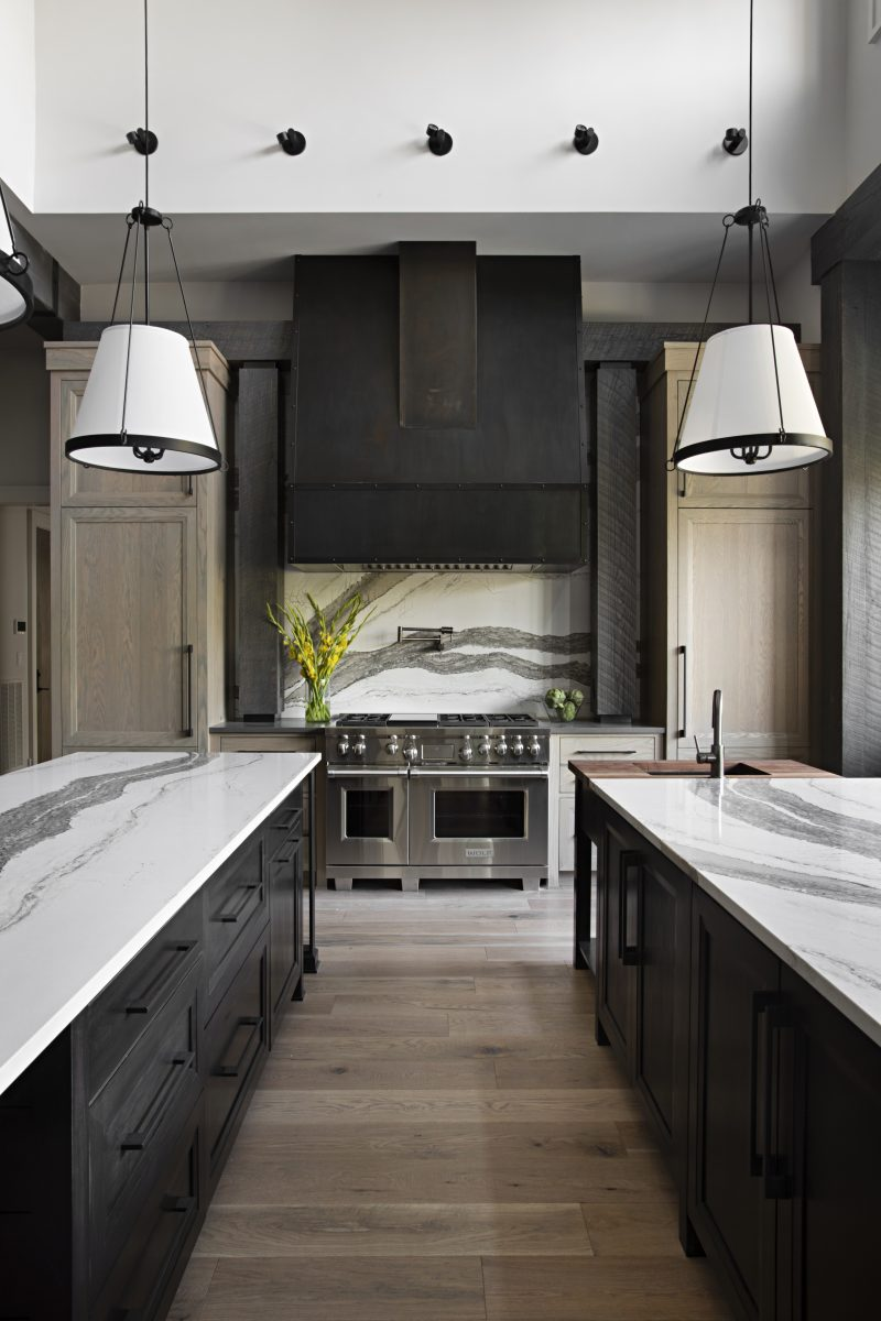 black and white themed kitchen with textured marble countertops, stove backsplash and oak cabinets and floors
