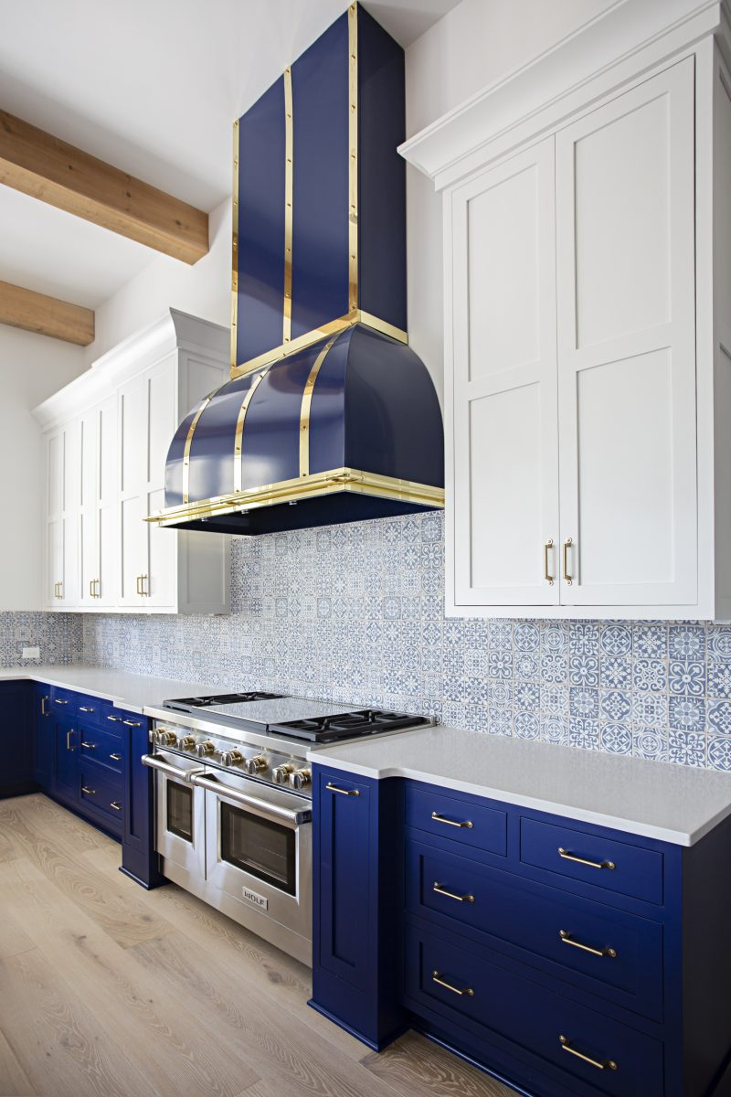 Blue kitchen drawers next to a stainless steel oven and blue stove cover with gold accent trims