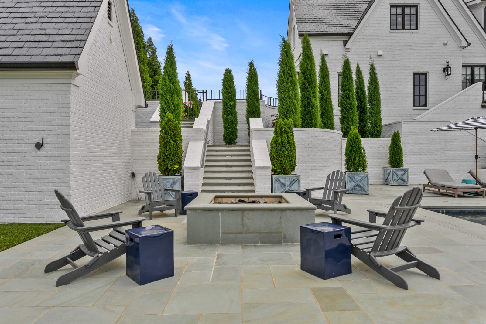Backyard fire pit in Franklin TN, with terraced stairs and tall evergreen trees