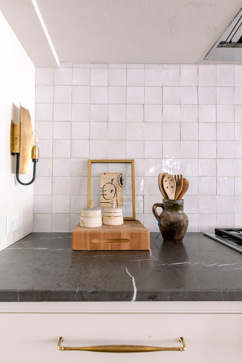 Kitchen counter top with dark grey marble or slate. White tiled backsplash
