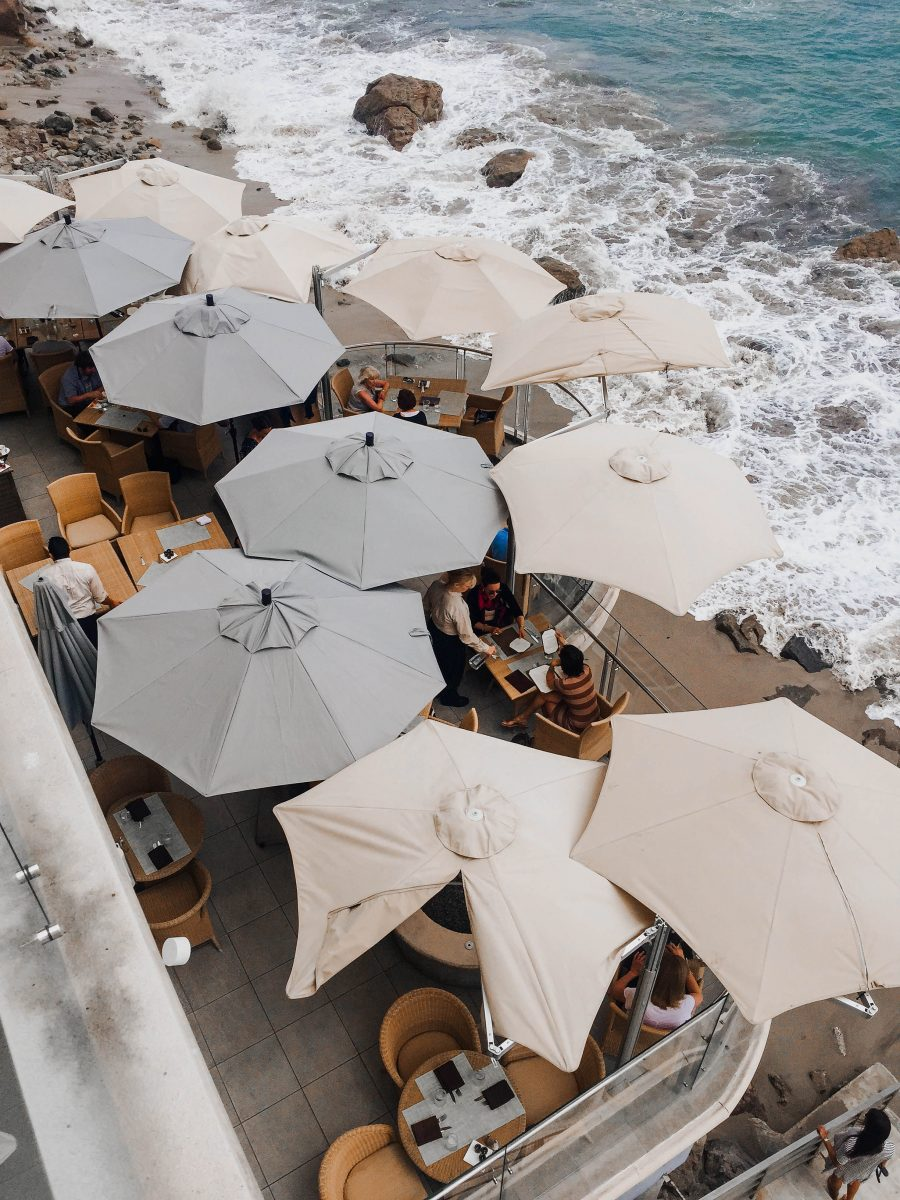 Shaded umbrella patio on a rocky beach, featured in the Nashville Edit.