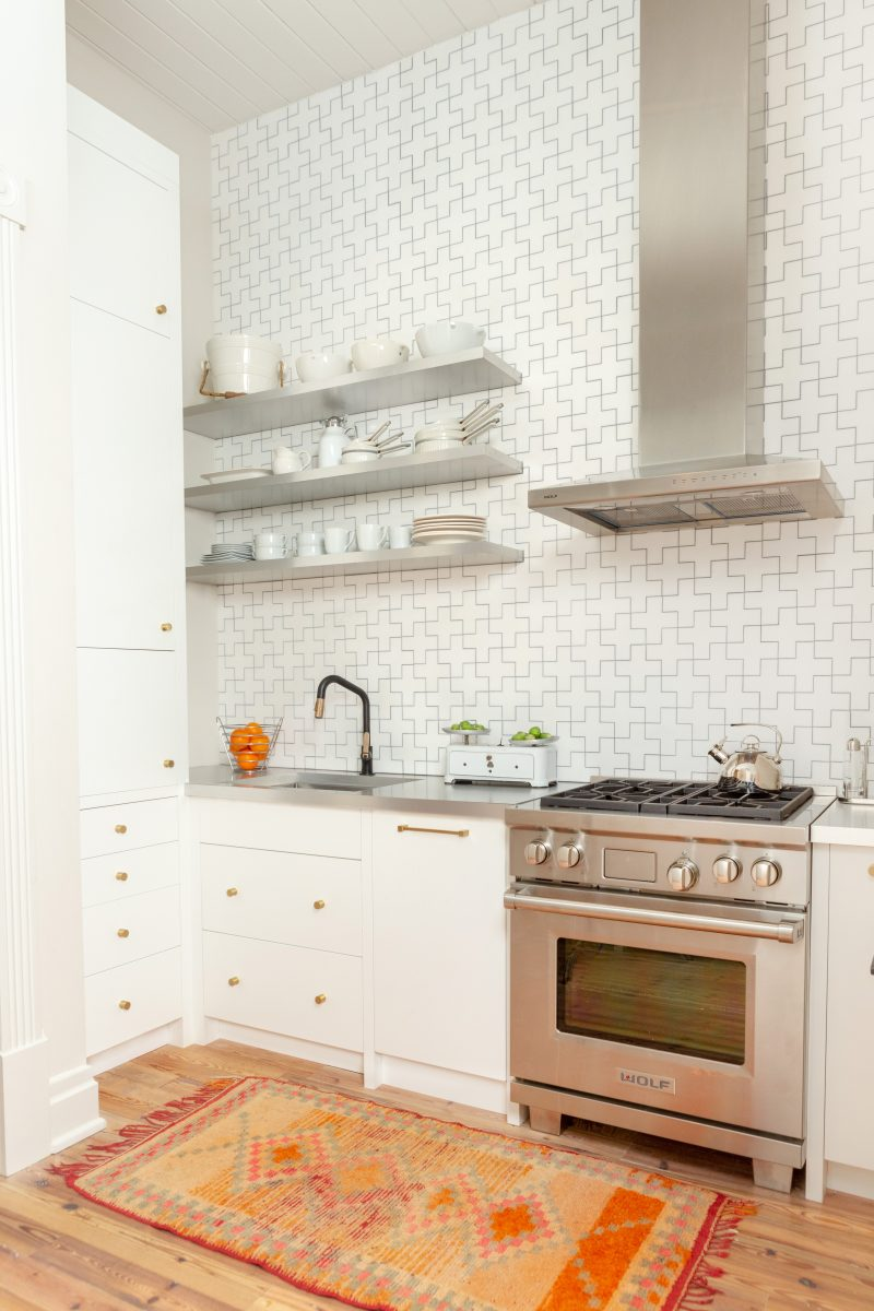 White tiled kitchen wall, white cabinets and a warm-toned rug to create a warm and welcoming home feel in the kitchen. Designed by Robin Rains