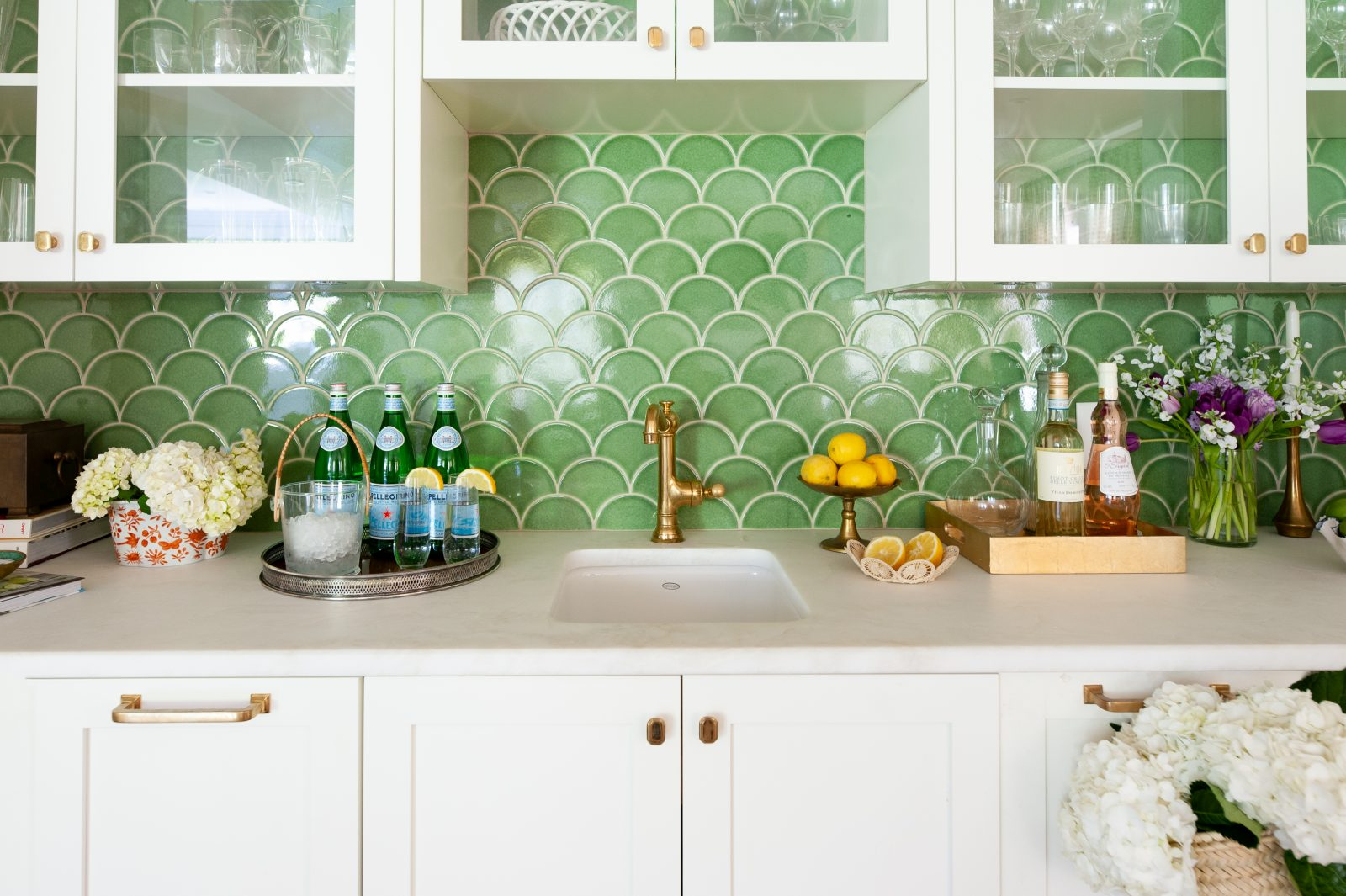 Green scale backsplash. White cabinets, gold accent colors.