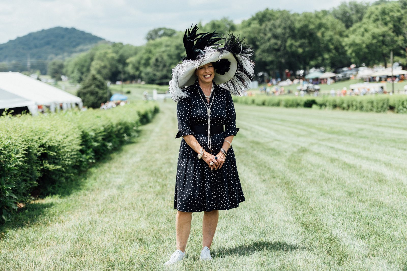 Diane Crooke in a black and white spotted dress with a black and white feathered hat
