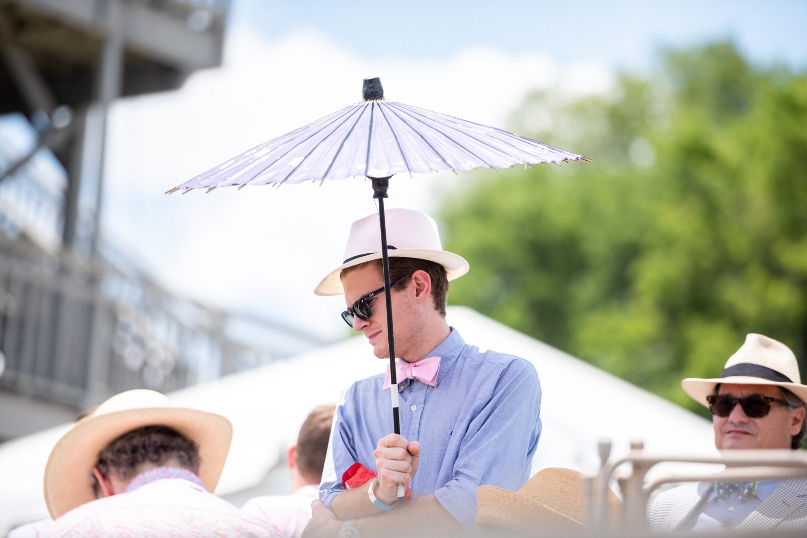 Man in a pink bowtie, blue button-up shirt, and white fedora at Steeplechase 21