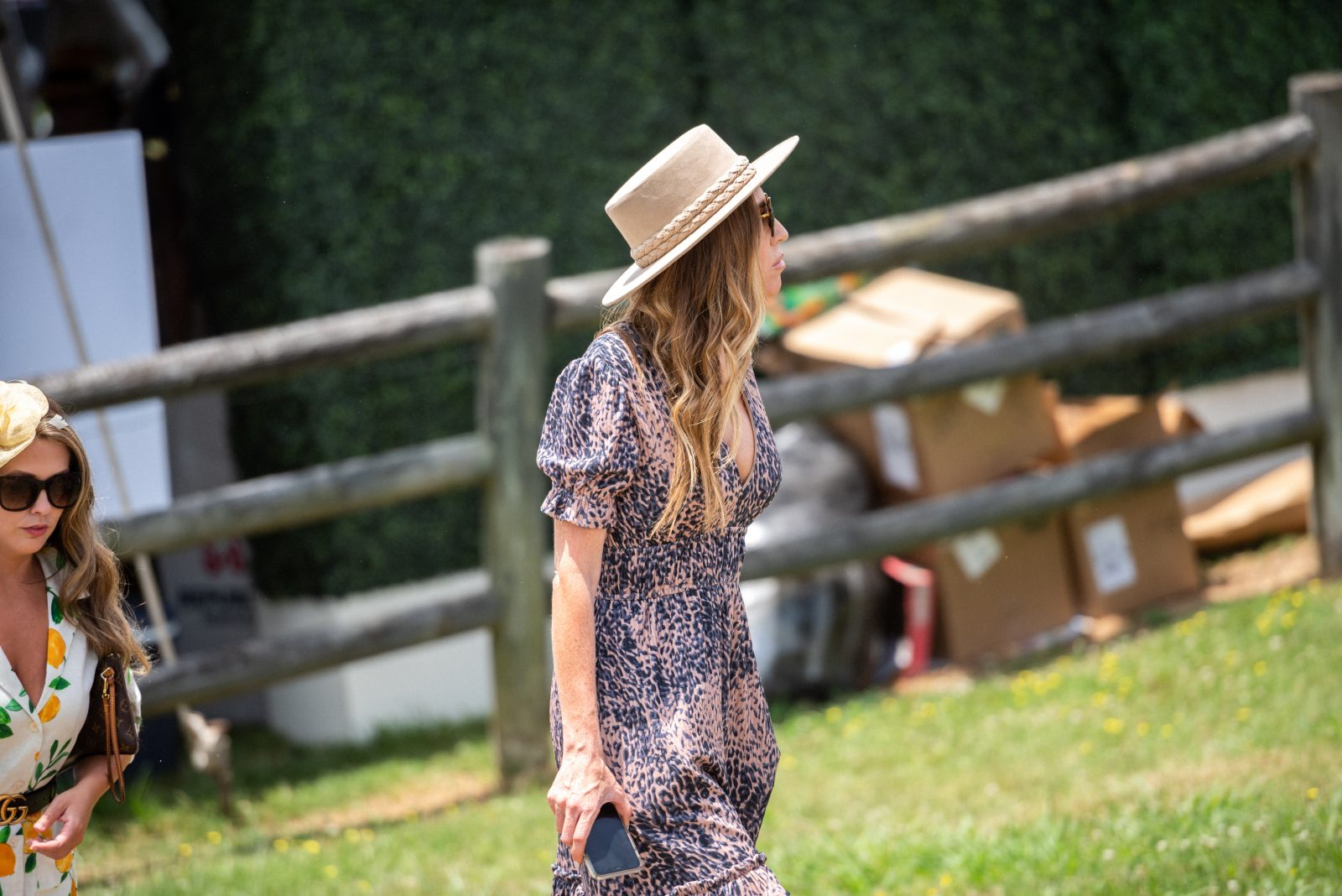 A woman with blonde hair, pink and blue dress, and brown hat at Steeplechase 21