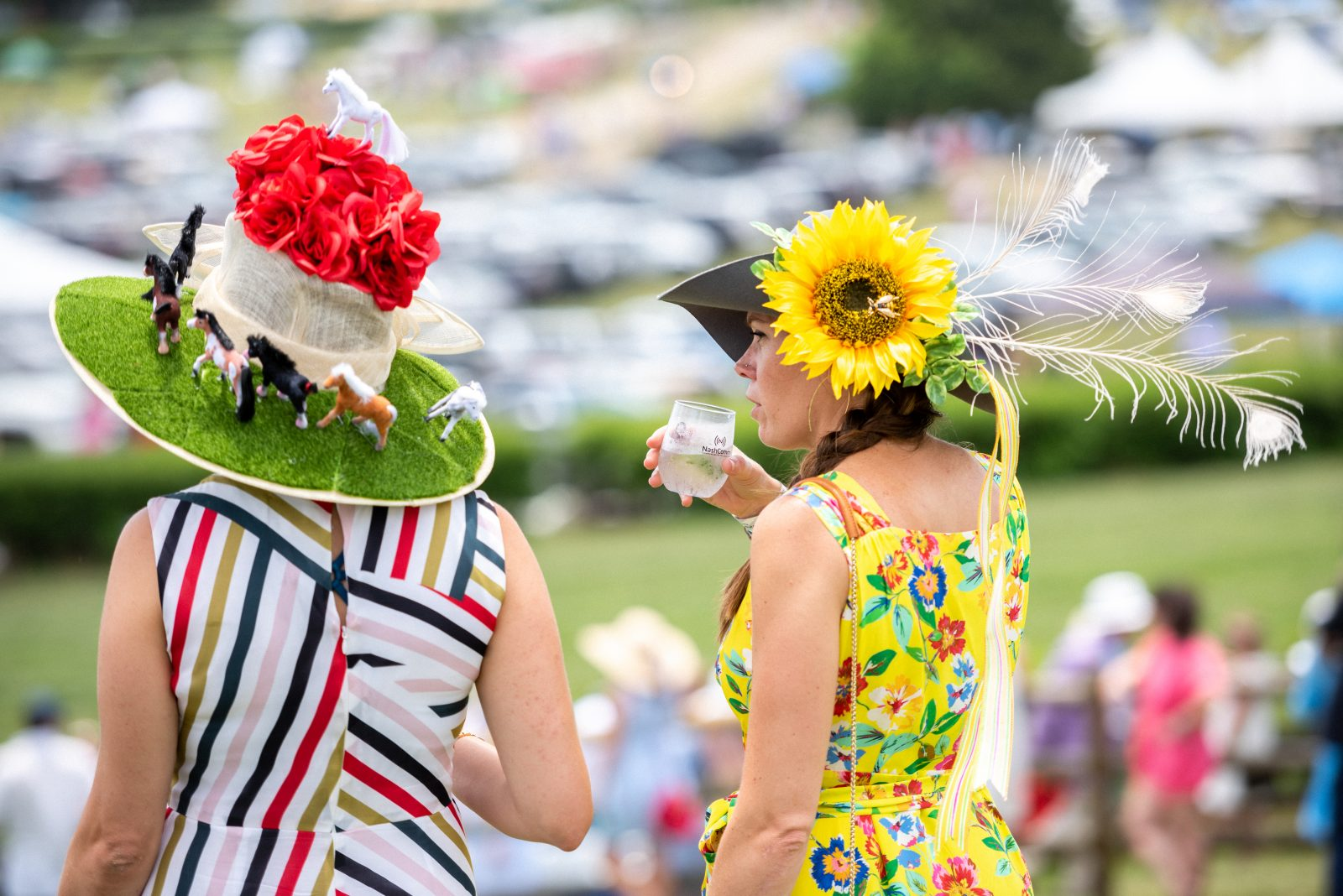 Two women, one in a striped dress and one in a yellow floral dress at Steeplechase