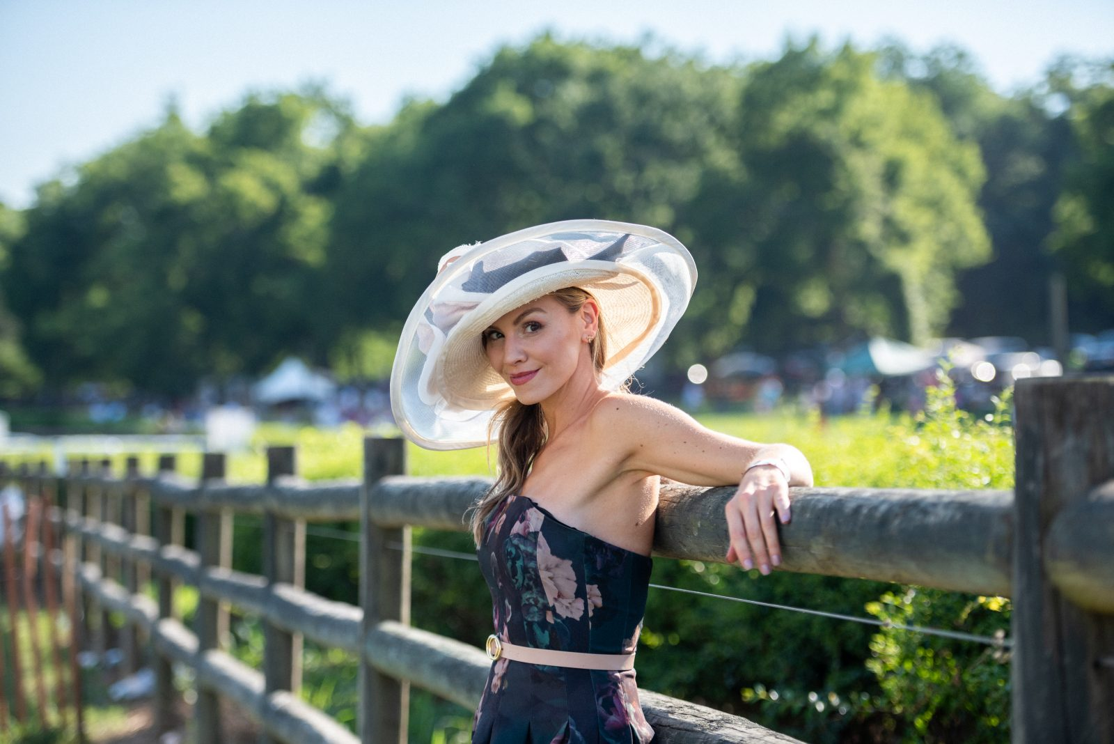 Woman in a blue floral silk dress with a wide-brimmed white and blue hat at Steeplechase 21