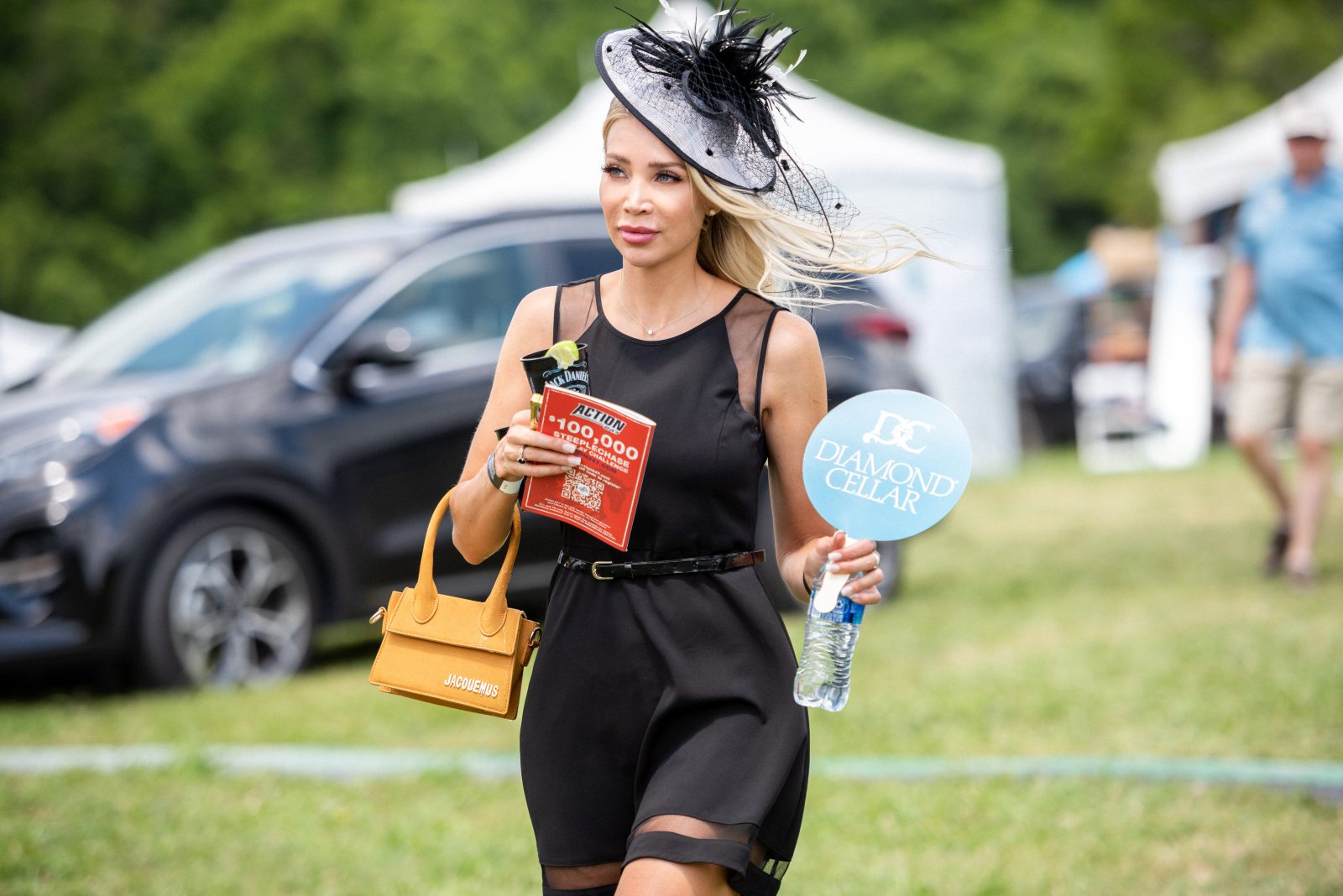 Kristen Theiben in a black dress, carrying swag from Steeplechase 21