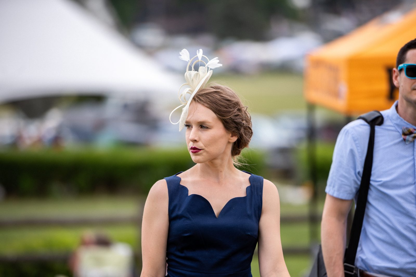 Caitlin Rantela with a navy blue dress and wearing a white ribbon fascinator.