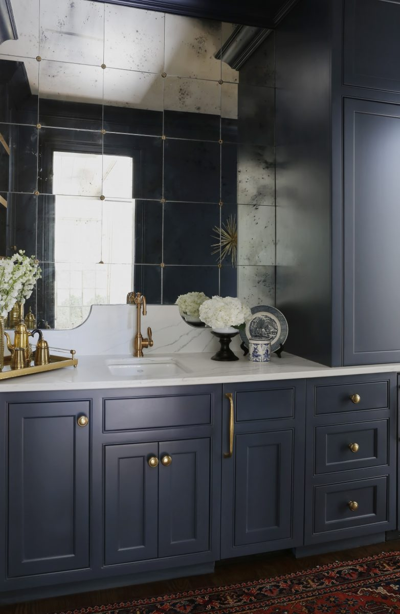 Navy blue painted cabinets and storage cupboards, gold sink and accent elements. Paneled mirror to add space. Built by Custom Home builder, Davis Properties in Nashville, TN