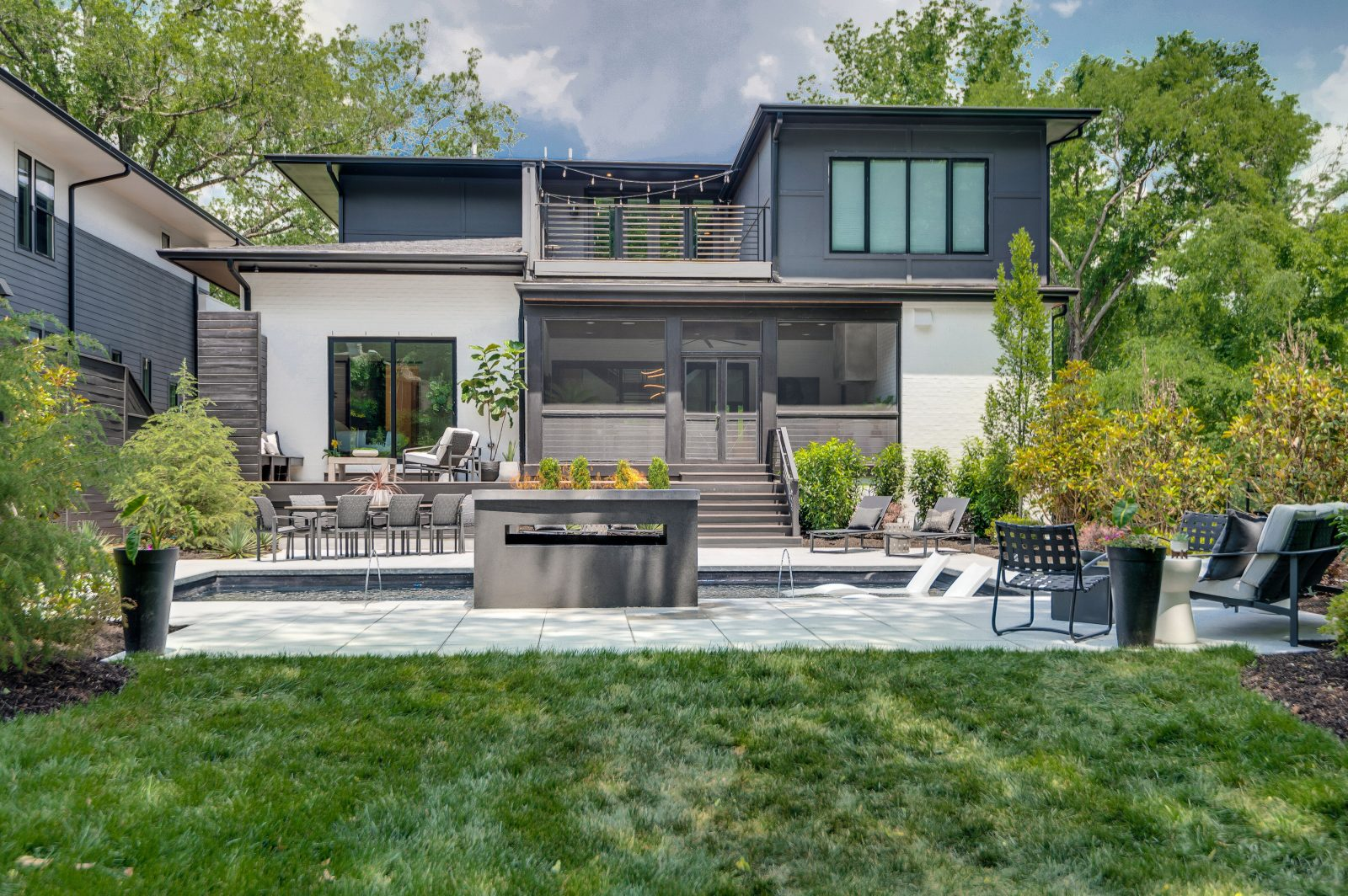 Rear elevation of backyard oasis with outdoor pool and fire pit in Nashville TN