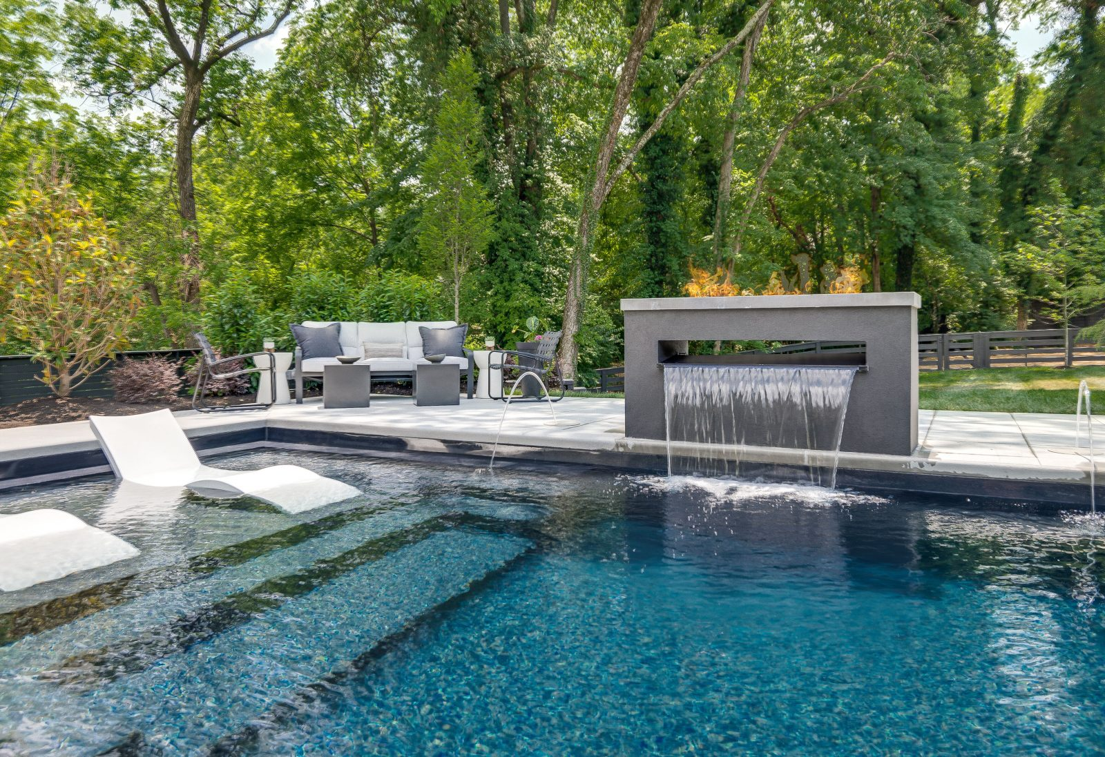 Relief of the central fire pit and waterfall fountain next to the pool.