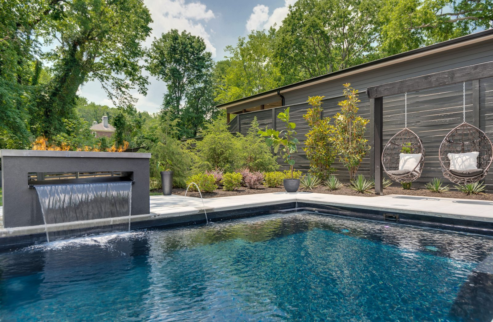 Angle of backyard pool, showing a small waterfall fountain into the pool, and two hanging pod chairs off to the right side.