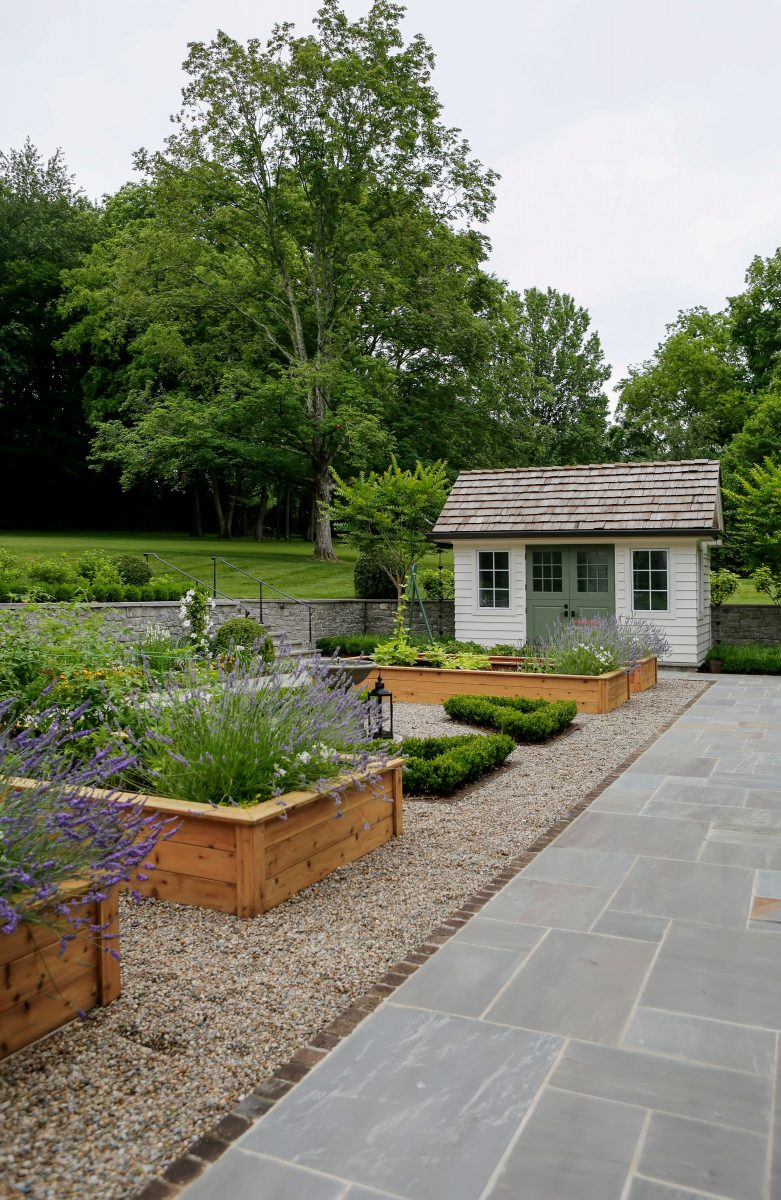 Beautiful backyard garden with shed, pea gravel, and herb garden boxes