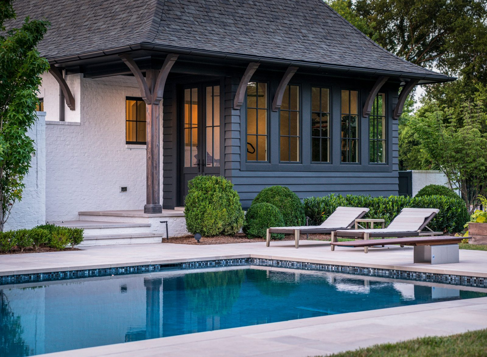Pool house and mudroom with an outdoor lounging space at this backyard envy worthy space