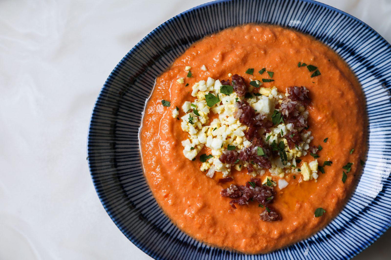 Tomato Salmorejo, Spanish foods, topped with egg, bacon, white marble table lola restaurant