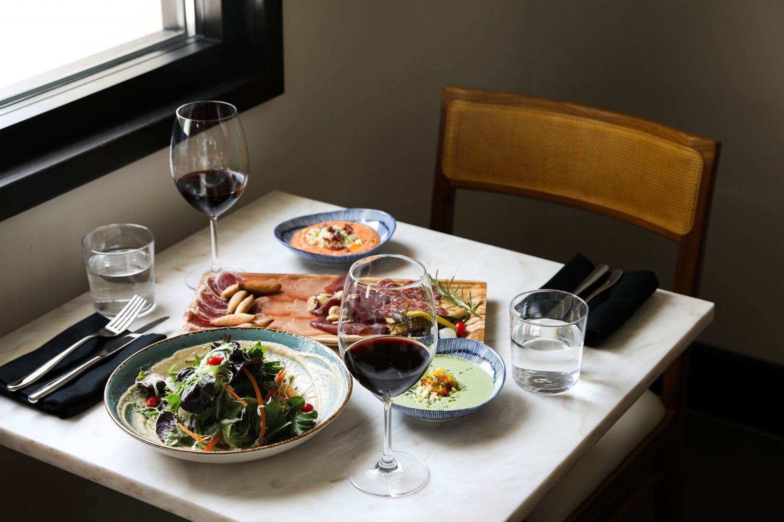 Pickled Piparra Salmorejo, Almendra Salad, Charcuterie Plate with spanish meats red wine simple minimalist restaurant white marble table wooden chairs