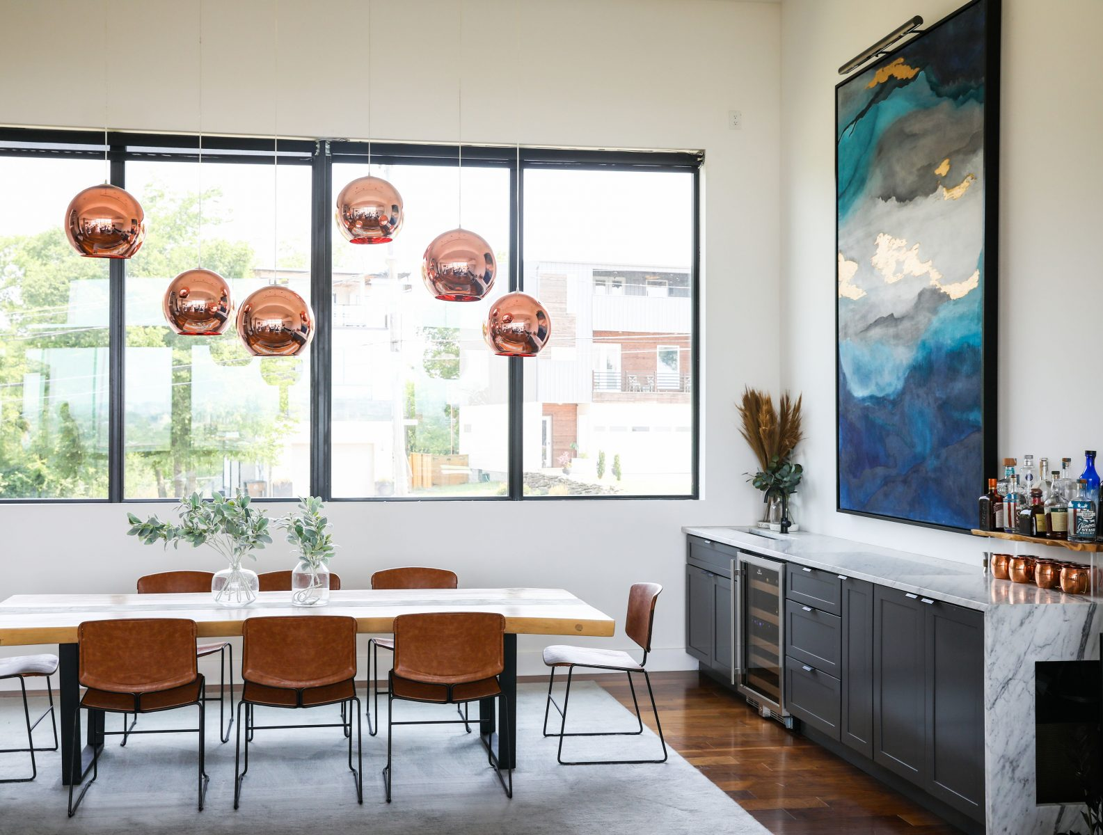 brooke and brice gilliam making modern magnolia network simple modern house wooden dinning room table blue artwork bar in dinning room neutral tones