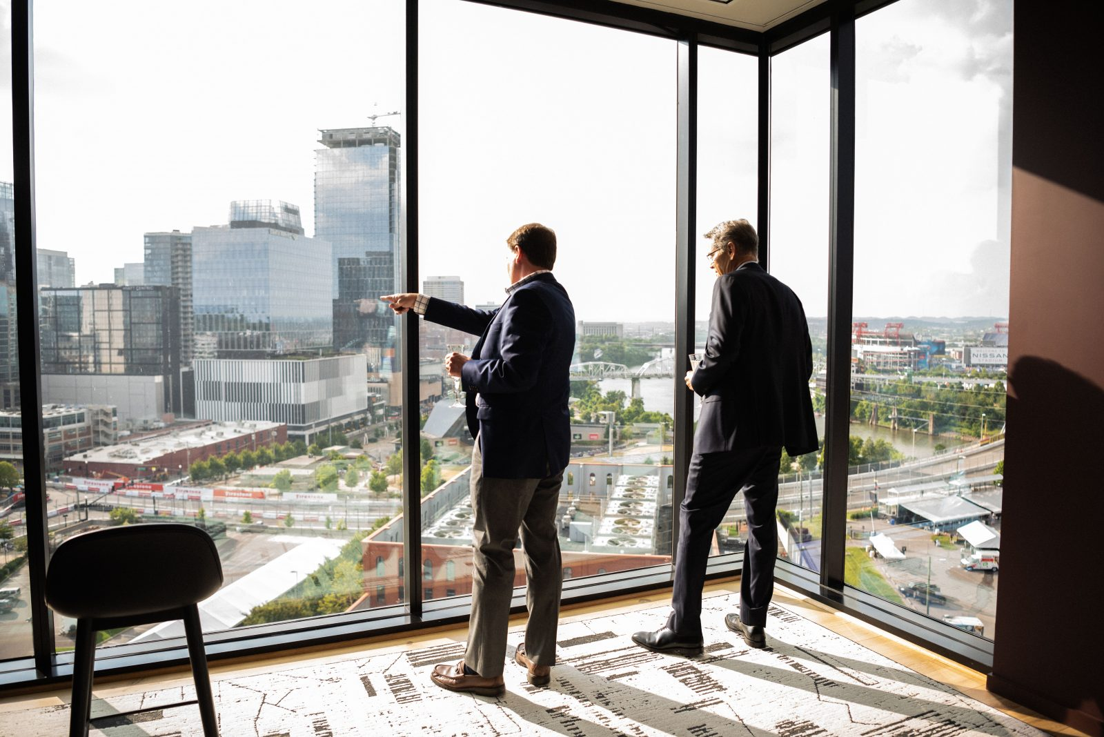 Charles Robert Bone and Cary Mack guys looking out the window of 4th capital at music city grand prix downtown nashville wine tasting