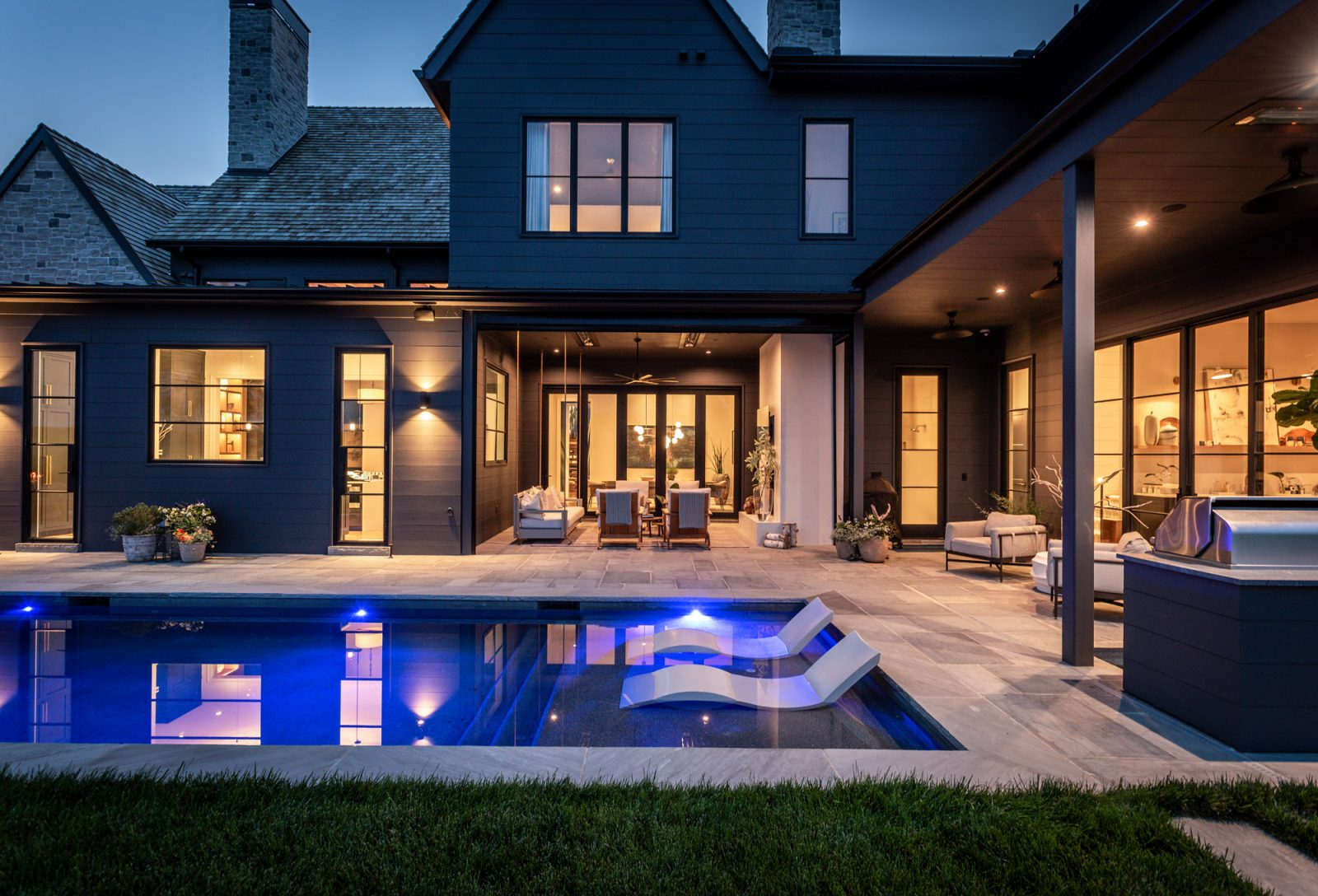 Covered patio outdoor design by marie-joe bouffard of jfy designs white outdoor chairs, porch swing outdoor sitting area fire place rondo pool with lounge chairs